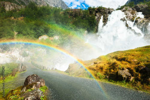 Kleivafossen waterfall with rainbow near Briksdal glacier in Norway.