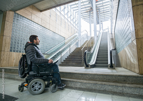 Photo Rear View Of A Disabled Man On Wheelchair In Front Of escalator and staircase wi