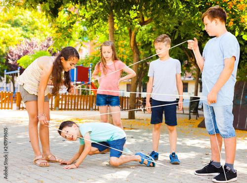 Fotografie, Obraz  children games. Girl goes through the tangled rope