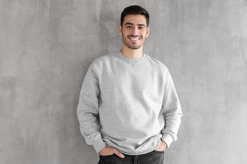 Young man in oversized sweatshirt isolated on textured gray wall background