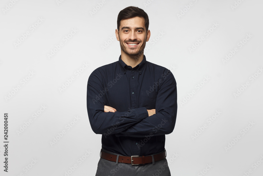 Fototapety, obrazy: Modern businessman in deep blue shirt standing with crossed arms, isolated on gray background
