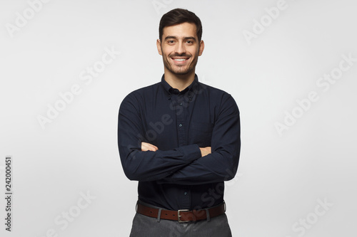 Obraz Modern businessman in deep blue shirt standing with crossed arms, isolated on gray background - fototapety do salonu