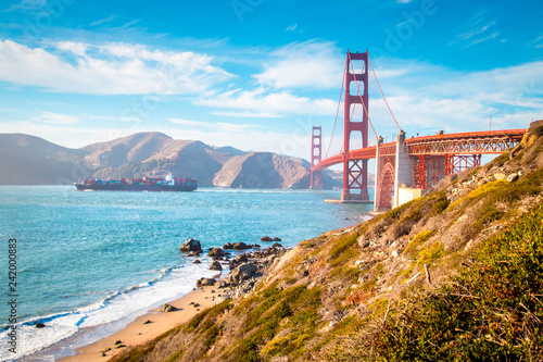 Keuken foto achterwand Amerikaanse Plekken Golden Gate Bridge with cargo ship at sunset, San Francisco, California, USA