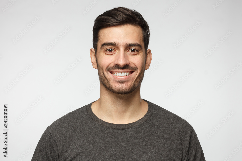 Fototapety, obrazy: Close-up portrait of smiling handsome young man in casual t-shirt, isolated on gray background