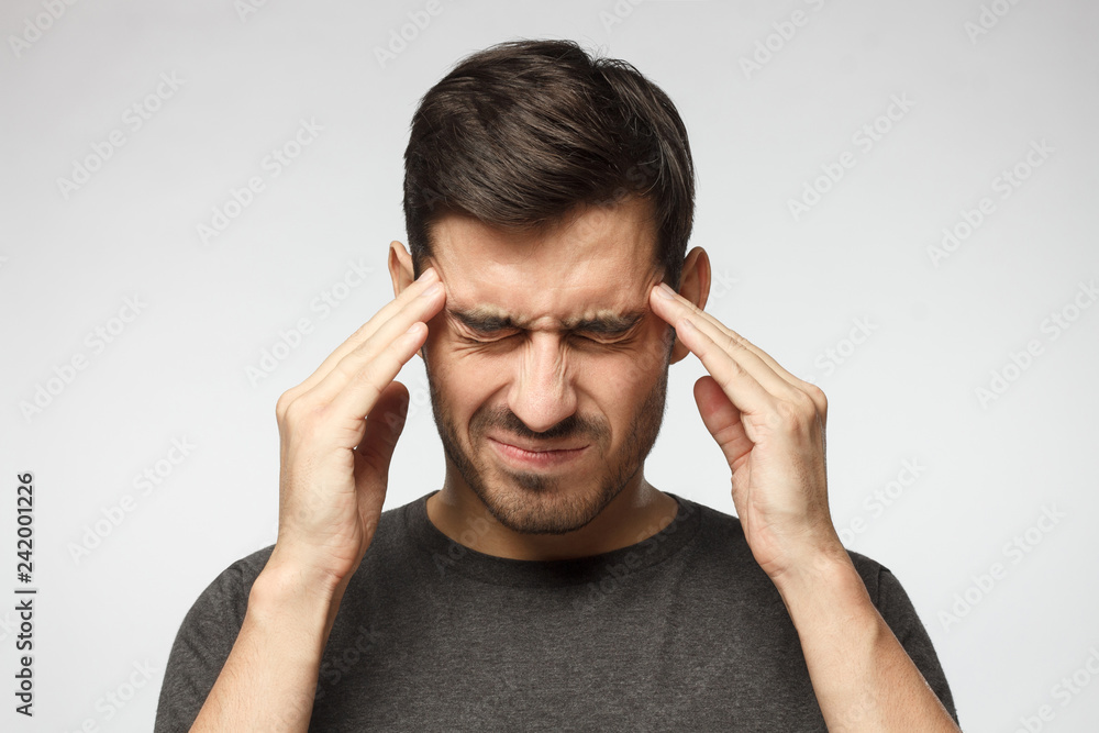 Fototapeta Portrait of young man isolated on gray background, suffering from severe headache, pressing fingers to temples with closed eyes