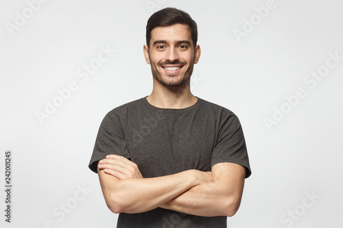 Foto  Smiling handsome young man in grey t-shirt standing with crossed arms, isolated