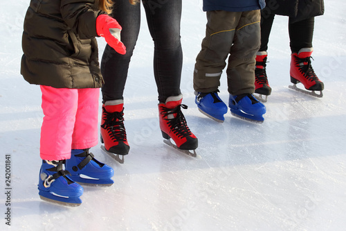 feet of different people skating on the ice rink