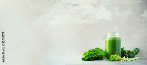 Photo  Bottle of green celery smoothie on grey concrete background