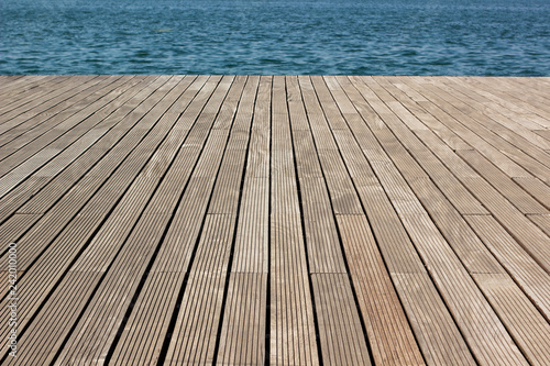 Fototapeta wooden deck floor waterfront shoreline background texture material perspective foreshortening surface to blue water, wallpaper pattern for copy or text obraz na płótnie