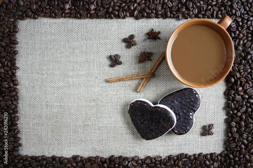 Fototapeta Filiżanka kawy, pierniki i cynamon, woków obramowanie z ziaren kawy obraz