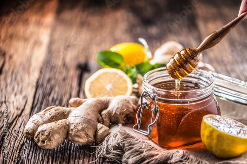 Fototapeta Honey jar dipper ginger lemon and mint herbs on wooden table obraz