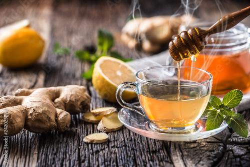 Fototapeta Ginger tea honey lemon and mint leaves on wooden table obraz
