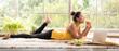 Leinwandbild Motiv Healthy Asian woman lying on the floor eating salad looking relaxed and comfortable