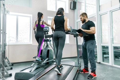 Young smiling fitness women with personal trainer an adult athletic man on treadmill in the gym. Sport, teamwork, training, healthy lifestyle concept