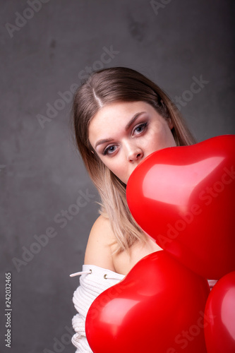 Photo  Young beautiful girl with red balloons in heart shape
