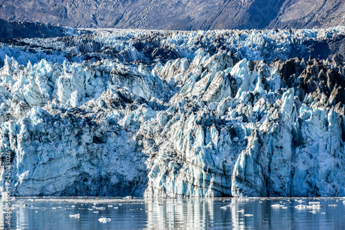 Fényképezés  Crevasses, seracs and other detail features of the Johns Hopkins Glacier in Alaska with small pieces of glacial ice floating in ocean
