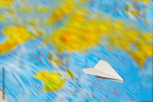 Fotografia, Obraz  A small paper plane flies over a blurred abstract geographical map of the world