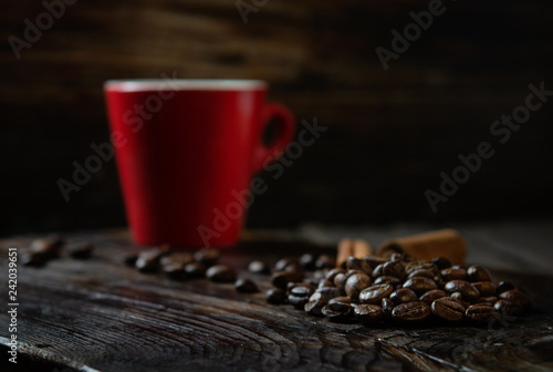 roasted coffee beans on wooden background with red mug, rustic style