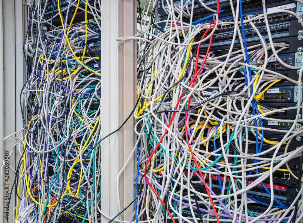 Fototapeta Switchboard panel with chaotic mess  cables connections, Chaos In Server Room, The tangled network cable