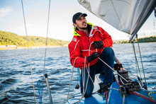 Beautiful Inspiring Shot Of Action Adventure Of Sailor Or Captain On Yacht Or Sailboat Attaching Big Mainsail Or Spinnaker With Ropes On Deck Of Boat, Sunny Summer Adventure Lifestyle