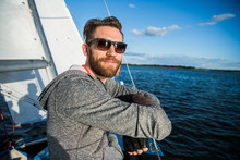Nice Happy Bearded Man Sailor Thumbing Up And Evincing Positivity While At His Yacht Or Boat On A River Or Sea.