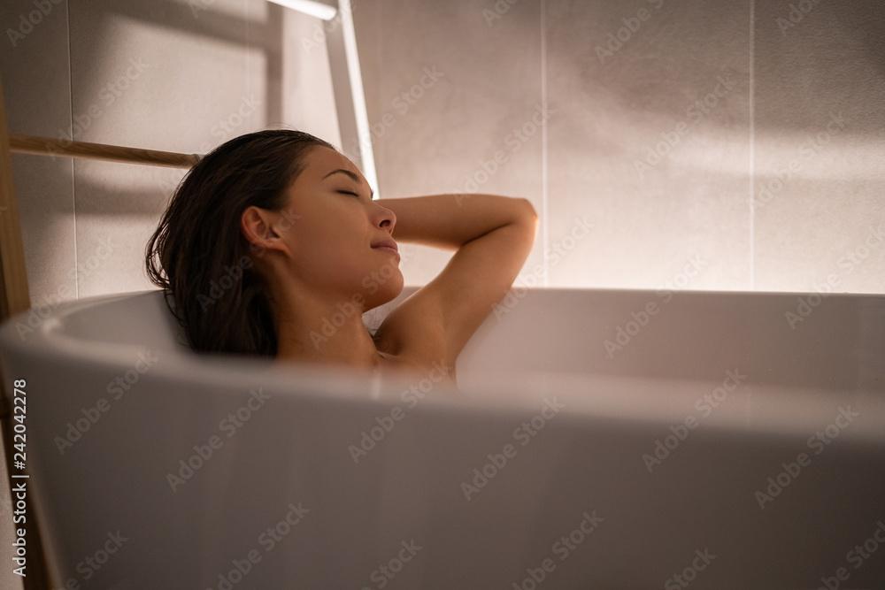 Fototapeta Luxury bath woman relaxing in hotel spa bathtub or home bathroom for total relaxation. Asian lady taking a bath sleeping in warm water, winter wellness.