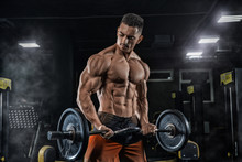 Young Handsome Sexy Man, Athlete, Bodybuilder, Weightlifter, In A Modern Gym Is Covered With A Dark Background, Doing Exercises For The Biceps Using Sporting Goods - Weights.