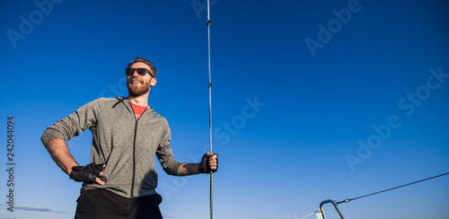 Fotografía  Young man wearing sunglasses standing on yacht stern and enjoying perfect autumn
