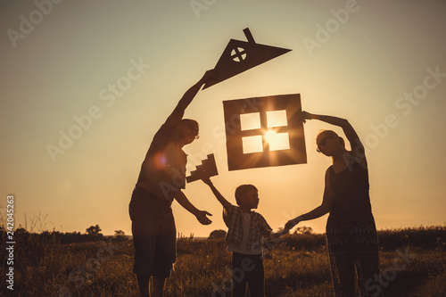 Obraz Happy family standing on the field at the sunset time. - fototapety do salonu
