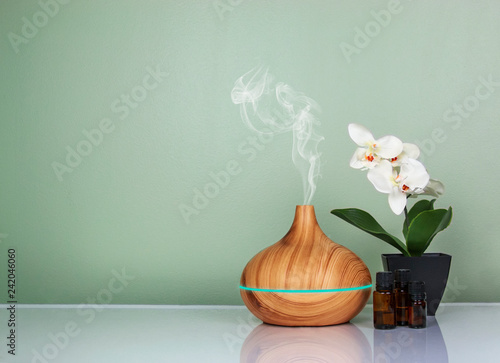 Fototapeta Electric Essential oils Aroma diffuser, oil bottles and flowers on light green surface with reflection obraz