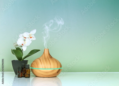 Tablou Canvas Electric Essential oils Aroma diffuser, oil bottles and flowers on green blue gr