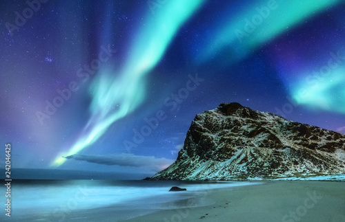 Cadres-photo bureau Aurore polaire Aurora borealis on the Lofoten islands, Norway. Green northern lights above mountains and ocean shore. Night winter landscape with aurora and reflection on the water surface.
