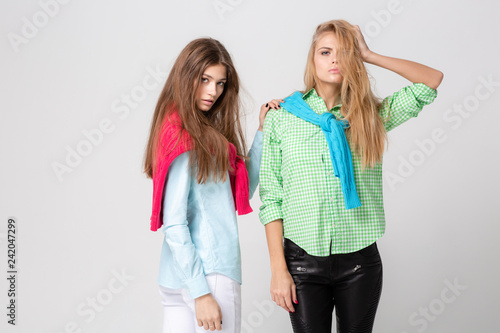 7b4c279c7f happy girlfriends women in shirts and a sweater on his shoulders. Fashion  spring image of two sisters. Colorful colors clothes. Models with Blonde  and light ...