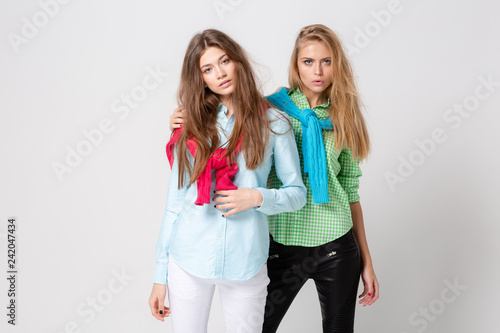 5cbf13141b Fashion spring image of two sisters. Colorful colors clothes. Models with  Blonde and light brown hair. Looking at camera and smiling.