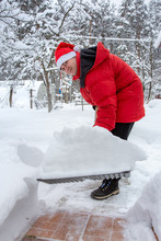 Man In Red Down Jacket And Red Hat Of Santa Claus Clears Snow In Backyard. Clears Snowdrifts On Path To Home. In Snowfall. Man Remove Snow With Big Plastic Shovel With Wooden Handle