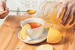 cup of tea with a lemon on a wooden table to which a spoon add honey