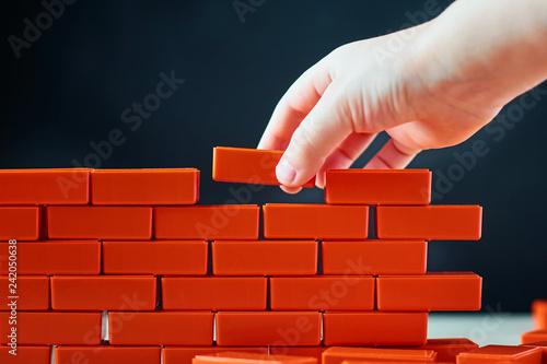 Hand puts last brick on wall Fototapete