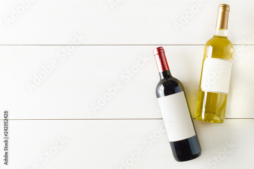 Fototapeta Red and white wine bottle on white wooden table flat lay from above obraz