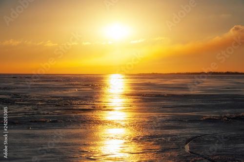 Fototapeta premium Zima krajobraz z zamarzniętym jeziorem i zmierzchu ognistym niebem. Skład natury.