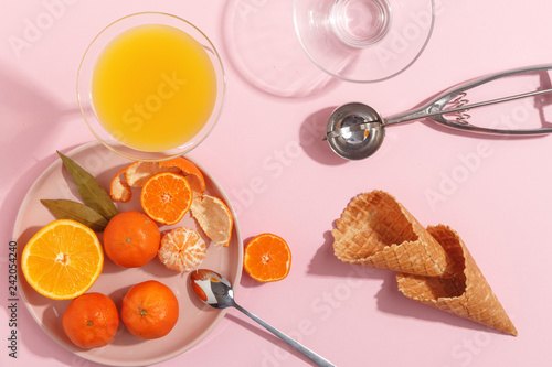 Fotografía  Tangerines, waffle cones and ice cream spoon on a pink background