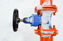 Industrial Shut-off Regulating Protective Pipe Fittings. Black Valve For Opening, Closing On An Iron Orange Metal Pipe With Flanges, Studs, Nuts Against The Background Of White Snow In Winter