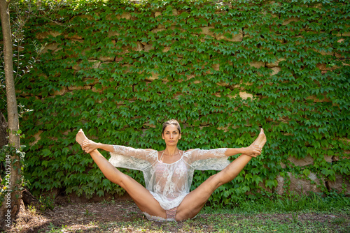 Obraz na plátně  Beautiful, young woman dressed in white romantic blouse practicing yoga in nature
