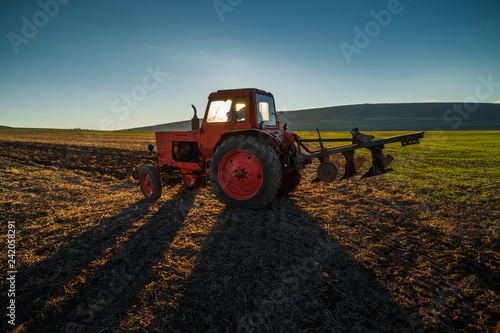 Valokuva  Tractor cultivating field at spring