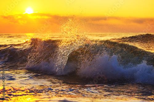 Fototapeta premium Złoty wschód słońca i rozpryskiwania niebieskie fale morza w pobliżu plaży