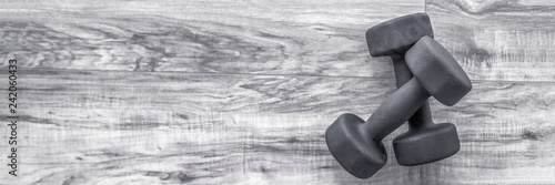 Fotografie, Obraz  Strength training exercise gym concept: dumbbell weights on wood floor fitness