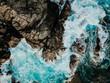 Vogelperspektive von Wellen die im Meer in eine Bucht mit Felsen strömen