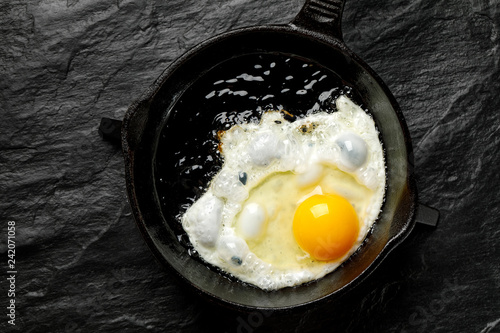 Fried egg on a black cast-iron pan, top view