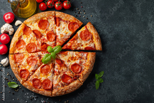 Cadres-photo bureau Pizzeria Tasty pepperoni pizza and cooking ingredients tomatoes basil on black concrete background. Top view of hot pepperoni pizza. With copy space for text. Flat lay