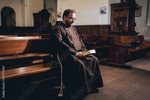 Fotografie, Tablou A monk in robes with holy bible in their hands praying in the church
