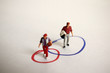 A miniature woman and a miniature man on the two overlapping circles in the other. The concept of gender discrimination in the community.